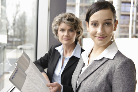 Businesswomen looking at brochure Stock Photo