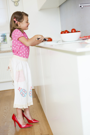 Girl cutting tomatoes in high heels