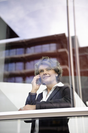 Businesswoman using cell phone, smiling