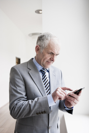 Businessman typing on Handheld