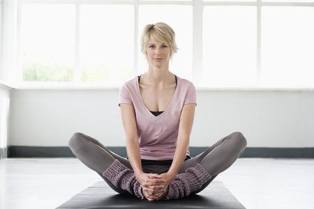Woman stretching legs on yoga mat Stock Photo