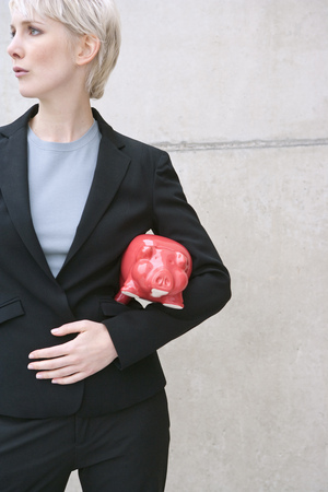 woman in suit with piggy bank Stock Photo