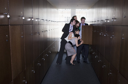 prying: Businessman with head in locker Stock Photo