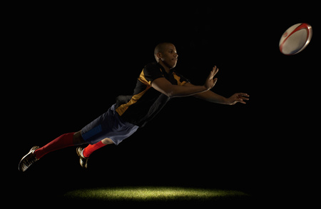 Rugby player diving whilst passing ball