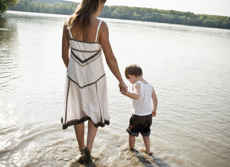 indecisive: Mother guiding child in river Stock Photo