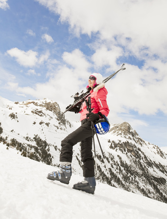 A woman walking on snow with skis Stock Photo
