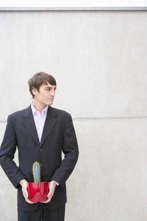 man in suit holding cactus