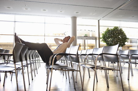 Businessman relaxing in empty conference Stock Photo