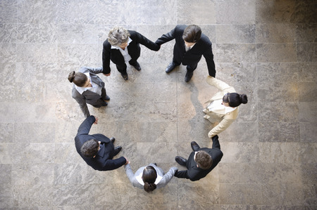 Business people holding hands in circle Imagens