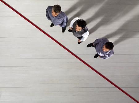 Bedrijfsmensen die zich door rode lijn bevinden