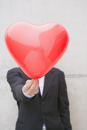 man in suit holding a heart balloon Banco de Imagens