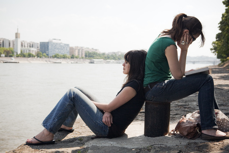 Two women sitting by river Stock Photo