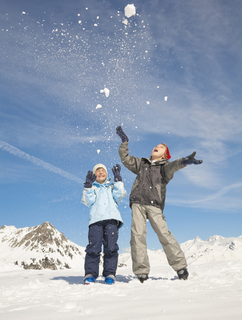 Two boys throwing snow in the air