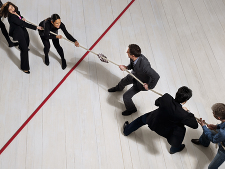 Business people playing tug of war