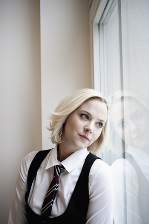 Businesswoman leaning against window