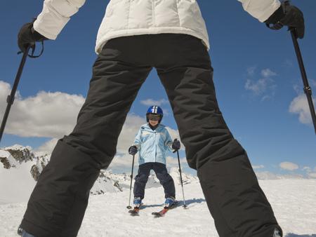 A woman teaching a boy to ski Stock Photo