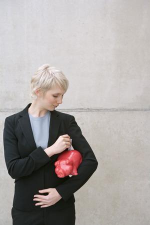 woman in suit with piggy bank Banco de Imagens