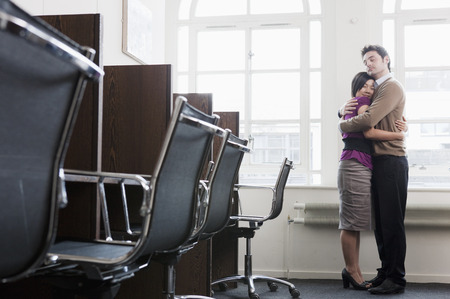 Couple hugging in a office Stock Photo