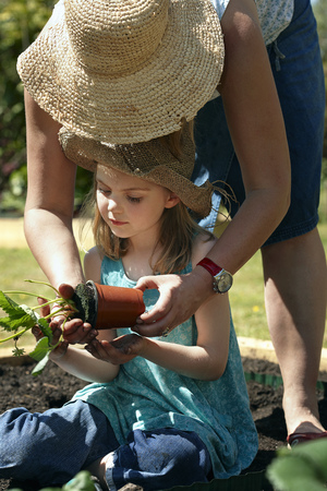 trusted: Mother and Daughter planting plants