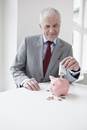 Man putting banknote into piggy bank Stock Photo