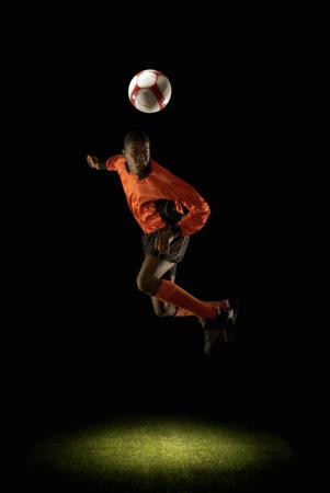 Footballer mid air heading ball Banco de Imagens - 86035375