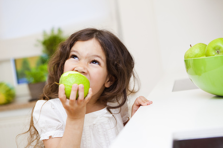 Girl biting a green apple Stock Photo