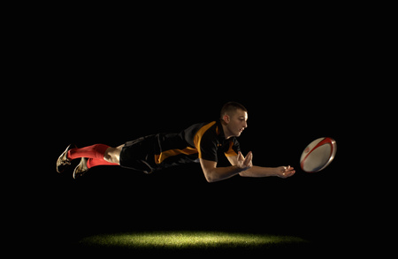 Rugby player diving and passing Stock Photo