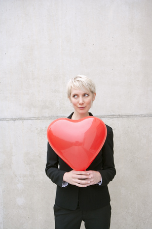 woman in suit holding heart balloon Stock Photo