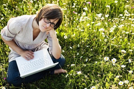 Woman with laptop in wild meadow Banco de Imagens - 86035404