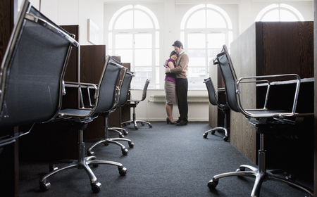 Couple hugging in a empty office Stock Photo