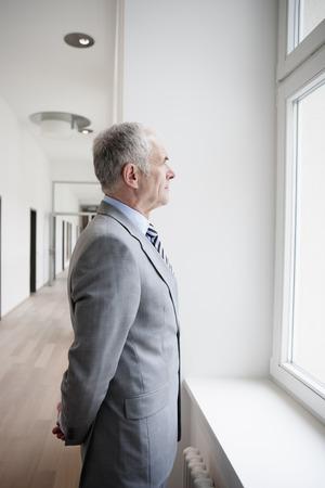 Zakenman kijkt naar het raam Stockfoto