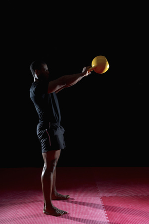 side view of man raising kettle bell