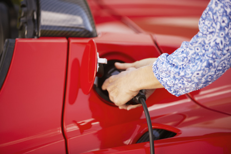 womens hands: Woman plugging in her electric car