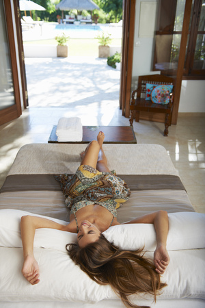 Woman relaxing on hotel bed Stock Photo