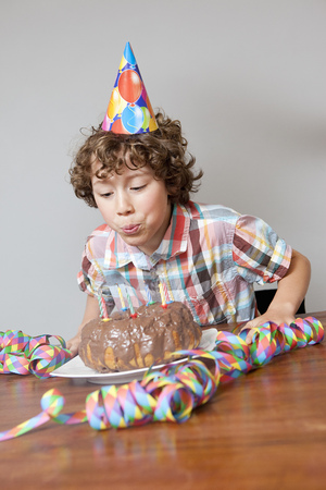A boy blowing out birthday candle Banco de Imagens