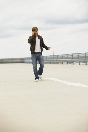 Young man on mobile phone on a parkdeck