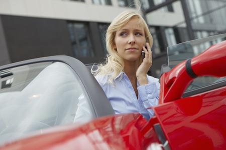 Femmes sur téléphone dans sa voiture électrique Banque d'images - 86035436