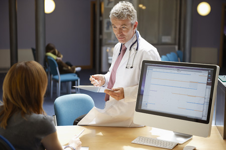 Doctor sitting on desk in reception