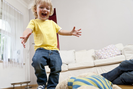 Boy jumping in living room Stock fotó