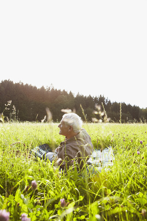 Senior man lying in meadows Stock Photo