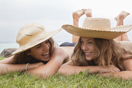 Women in straw hats laughing together Stock Photo
