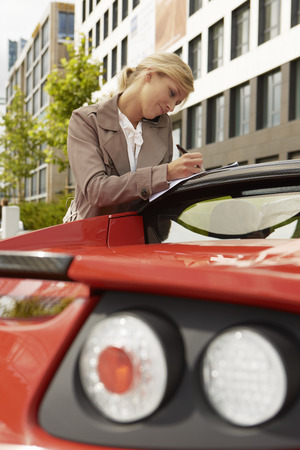 Business woman on mobile phone with car