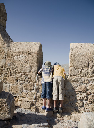 Two boys looking over wall at view