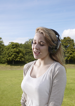 Girl singing along to headphones Stock Photo