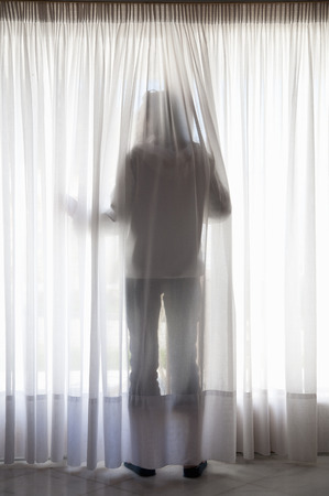 Silhouette of figure through curtains