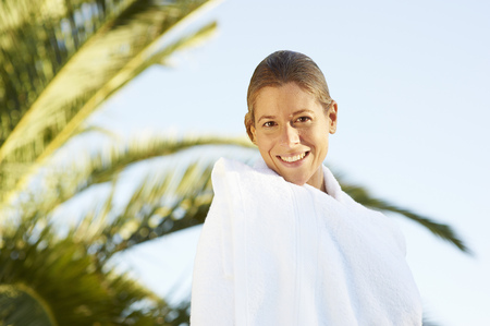 Girl wrapped in towel by the pool