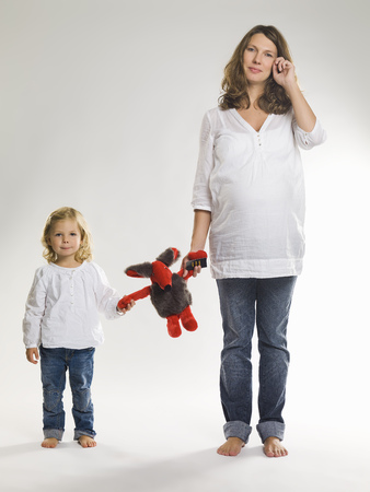 Pregnant woman and daughter holding toy