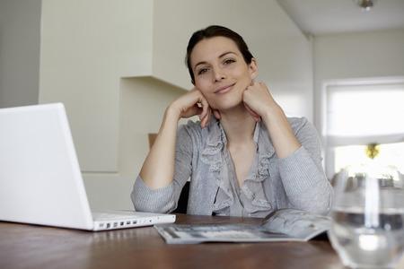 Woman using laptop in living room Banco de Imagens