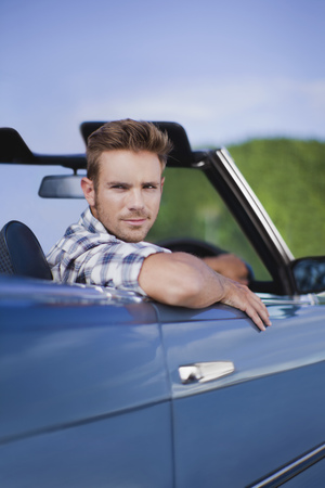 Man peering out of convertible