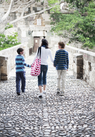 Mother walking with two boys Stock Photo